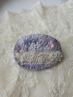 Wild Meadow embroidered felt brooch with antique lace    Hand embroidered wild meadow flowers on a piece  of Irish felt that has a mottled and very tweedy look.  The natural tones in the felting gives the background  bedding for the flowers.  Blanket stitched to deep purple felt backing.    I added some pretty antique Edwardian lace across  the brooch for some history.    Size: 50mm x 40mm (2inch x 1+1/2in) approx