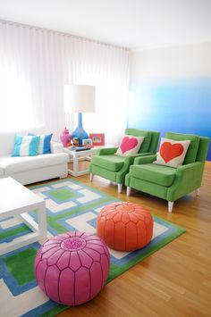 What a gorgeous and colourful room. Love the love heart cushions and the blue ombre painted wall!