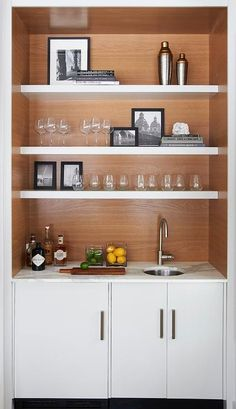 Amazing wet bar features white cabinets topped with statuary marble fitted with a round bar sink and satin nickel gooseneck faucet by Moen placed under stacked floating shelves.