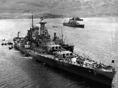 The covering forces of the PQ-17 Convoy (British and American ships) at anchor in the harbor at Hvalfjord, Iceland, May-June 1942. Washington (BB-56) in foreground loading supplies with HMS Norfolk in the rear. Wichita (CA-45) is in the middle.