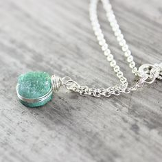 This tiny and understated necklace features a small light green turquoise druzy quartz circle bead that hangs from delicate and lightweight sterling