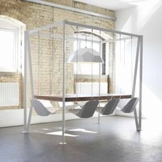 Putting a little extra fun into dinner time and boardroom meetings, this four poster table uses its structure to suspend a central GEO lampshade and eight hanging chairs that sway playfully.  Duffy London - Swing Table
