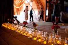 Wedding reception entrance with flowers, candles, and mason jars