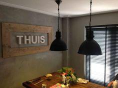 Zwarte industriële hanglamp in huiskamer met stoere sfeer: grijze beton look muren, zwarte jaloezieën en hout.