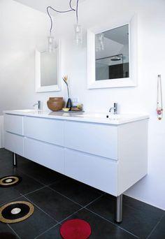 Baderommet er enkelt og moderne innredet med hvite flater, og mørke fliser på gulvet. Morsomme, små, runde tepper ligger spredt rundt på gulvet.