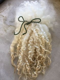Lovely lovely locks.  Each bundle is an ounce of Masham long locks. Masham are a cross between a Teeswater or Wensleydale ram and one of several varieties of ewe. Locks are clean and separated and free of vm. There is some yellowing at the tips but the fiber is strong and maintains its curl. Some locks are super curly and some more open. Staple length varies from 10-12 inches long unstretched with some shorter and some longer. I have done my best to make sure each bundle is the same.   These…