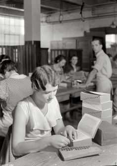 """November 1933. Kingsport, Tennessee. """"Ola Brooks of Mount Carmel. This girl is placing index tabs, applied with tweezers. A moderate degree of skill is required to get tabs in the right place and in the right position. This girl came to the Kingsport Press directly from a farm and has been working only two months."""" Another of Lewis Hine's photos for the Tennessee Valley Authority"""