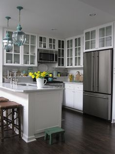 Love the floors, the window pane cupboards, the bright white with subtle hints of color, and even the fridge. Just LOVE.