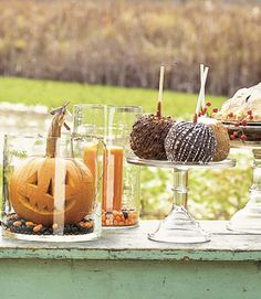 Fall center piece idea. Large carved pumpkin in large glass cylinder , add pumpkins on top of cake platter - place other orange candles in glass cylinder vases.
