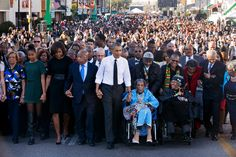 President Barack Obama, center, walks as he holds hands with Amelia Boynton, who was beaten during