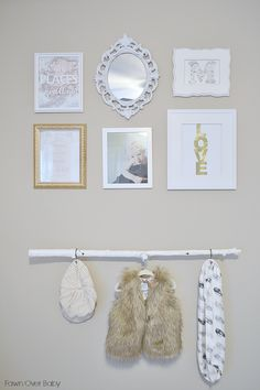 Gallery wall with gold accents - and we love the fab baby clothes displayed! #nursery #gallerywall