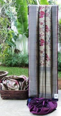 This tan coloured Benares tussar has a floral pattern in purple, red and navy blue. The border is in navy blue, purple and tan.The pallu is in tan and navy blue giving it a distinguishing finish