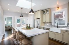 Contemporary Kitchen with Breakfast bar, Skylight, Stone Tile, Flat panel cabinets, Kitchen island, One-wall, Farmhouse sink