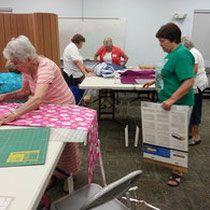 Members of Creative Sassy Sewers NG prepare kits for Summer Camp