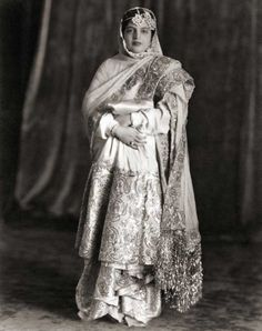 Portrait of Princess Rafat Zamani Begum, c. 1960. Portrait of Princess Rafat Zamani Begum of Rampur (1907-1987), wife of Nawab Raza Ali Khan, taken by the famous Kinsey Brothers studio of Delhi. Part of her garment is the typical Farshi pyjama, worn by Muslim women between the 17th and 20th centuries, entailing a two-legged skirt that fell to the ankles and then trailed the floor. It required the wearer to fold parts of it over the left arm while standing or walking.