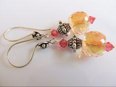 Oorbellen Nance glaskralen facet roze-oranje met roze swarovski en mooi bewerkte zilveren kraal en oorhaken met zilverstippen ornament. geheel zilver. www.doloressieraden.nl