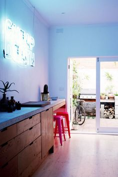 """Source: Homelife Im pretty sure that neon sign says """" Cheap Death"""".not sure thats what I would choose but each to their own. I secretly still love it! and the wonderfully bright Tolix stools."""
