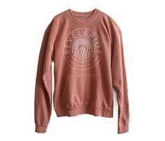 The Revel & Riot emblem on a comfy clay color washed sweatshirt. $60 in the Revel & Riot shop!