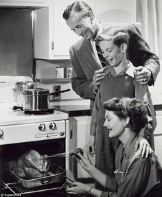 Family feast: Father and son look on as mother bastes the turkey during a traditional Thanksgiving dinner. #vintage #Thanksgiving #holidays #turkey