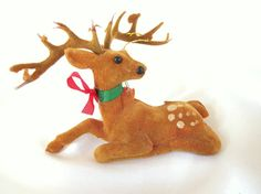 Vintage brown flocked plastic deer Christmas ornament sports a large rack of antlers that are shedding their velvet. He has black plastic eyes