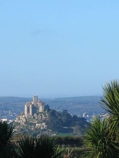 The low winter sun on St Micheal's Mount in Corwall set against a powder blue sky