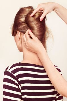 This updo is that rare style that can go timeless or edgy, elegant or breezy. Create it in five easy steps. Here, step 4: Bring the loose lengths over to the left, roll ends under, and pin.