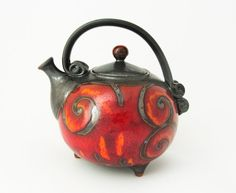 You are bidding on unique red fire teapot.    This teapot is handmade in small art pottery studio in eastern europe.    Made of black clay and hand