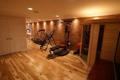 """""""I'm not sure why but I love the home gym designs which utilise smaller spaces. Matthew Bowe Design uses exposed brick on the back wall with the delicately placed down lighting bringing out its natural warmth. You can see in the corner a sauna unit, compact and perfectly placed. The wooden floor gives a solid sanitary gymnasium feel to the room."""""""