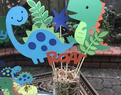 Dinosaur centerpiece comes with two large dinosaurs Two leaf accent pieces Roar accent piece Also available to match this theme Cupcake toppers Happy birthday banner Goodie bags High chair banner Dinosaur First Birthday, Dinosaur Party, Baby Birthday, Baby Dino, Birthday Party Centerpieces, 3rd Birthday Parties, Baby Party, Creations, Baby Shower