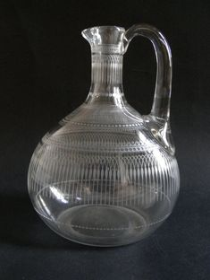 Jug, clear glass, blown, flattened oval form, engraved with a frieze of arches and scrolls on body and neck.