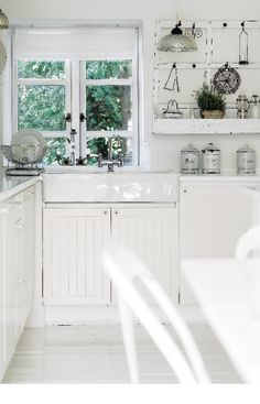 In the kitchen, an old coat hanger hangs between the windows. Kitchen cabinets, sink and faucet, Ikea.