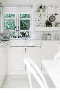 I köket hänger en gammal klädhängare mellan fönstren. Köksskåp, handfat och blandare, Ikea.