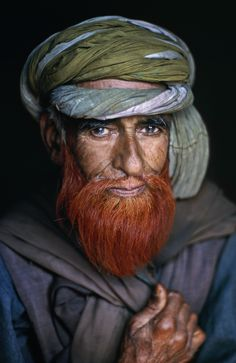 It is common for men in Kashmir to use henna dye on their hair or beards.   They also wear clothes of vivid colors. A subtle mix of colorful fabrics surrounds the man's  eyes, while his beard, like a flame, flickers from his chin.