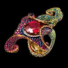 FLOWERS HIGH JEWELLERY RING 18K yellow gold 1 oval ruby 5,93 ct 20 diamond 0,11 ct 127 green diamonds 1,05 ct 108 blue diamonds 0,77 ct 228 rubies 1,66 ct 134 sapphires 1,08 ct
