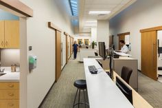 An open/offstage staff teaming area is implemented within the Warren Clinics to provide more privacy, increased efficiency, and discreet access into each exam room, with patients accessing the room from an adjacent door off of a public corridor.