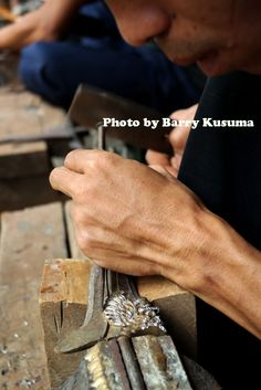 A keris craftsman working on the intricate details of the keris blade.