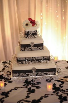 Pretty... Black and white cake with red and white gerbera daisies.