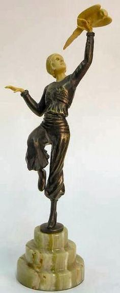 A bronze Art Deco style sculpture, girl on onyx base, with composition head and arms. After Dimitri Chiparus (Romanian, French, 1886 to 1947; active Paris, 1914 to 1933).