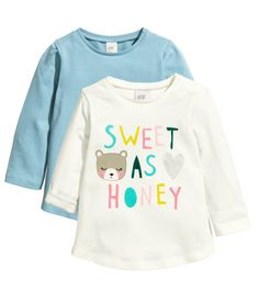 Long-sleeved tops in soft cotton jersey with a gently rounded hem. One top with a printed pattern.