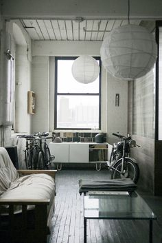 An ancient motorcycle and a rack of bicycles in a tiny, tidy studio space