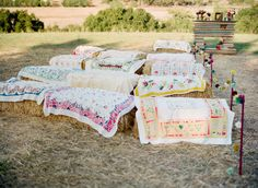 ahh...vintage table cloths over bales of hay! and a makeshift fireplace mantle down the aisle