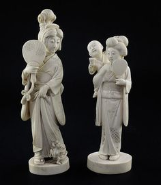 Two Japanese ivory groups of bijin, early 20th century, the first of a lady holding a fan and pulling her robes away from a frog clambering at her feet, two character signature to a red lacquer seal, 23cm., the second of a lady with a child on her back, engraved two character signature to base, 19cm.