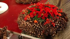 Holger Schweizer gestaltet eine weihnachtliche Dekoration aus Zapfen und Weihnachtssternen.