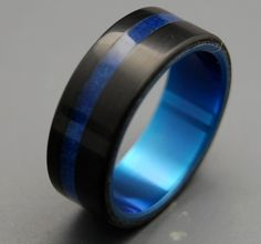 Black and blue wedding band Tron Titanium Resin Wedding Band by MinterandRichterDes on Etsy. $325.00 USD, via Etsy. - very cool, but wonder if I could find one with peridot...