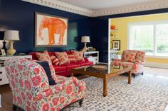 The upholstery fabrics, the spotted rug, the framed elephant, the dark walls with contrasting crown moulding, I love it all.  By Hannah Childs.