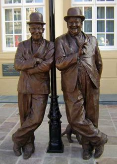 Life-size bronze portraits of Stan Laurel and Oliver Hardy with their dog 'Laughing Gravy' sited in Stan's birthplace Ulverston, Cumbria, UK. Commissioned by The Sons of the Desert and unveiled in 2009
