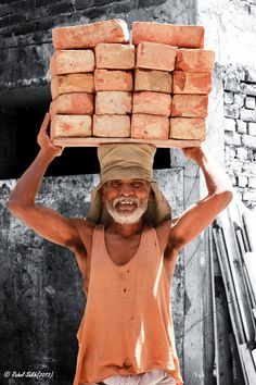 Man carrying a heavy load of bricks in India -- with a smile!