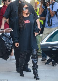 Trendy: Kim showed off a white manicure as she stepped out in the eye-catching, thigh-high boots