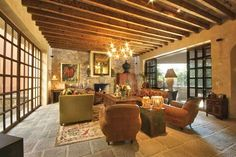 Formal living room with stone walls, windows, carved stone fireplace and access to the terrace dining room #agavesanmiguel #sanmiguelrealestate