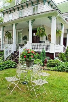 Green hanging baskets, iron table and chairs, statue -- lovely lush front porch and yard
